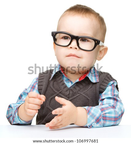 Portrait of a cute little boy wearing glasses, isolated over white