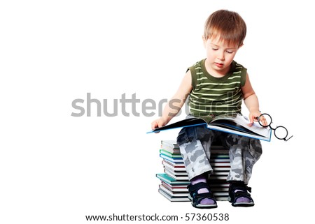 Portrait of a cute little boy with books. Isolated over white background.