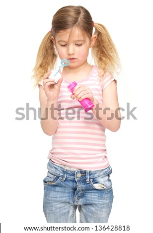 Portrait of a cute little girl blowing soap bubbles isolated on white