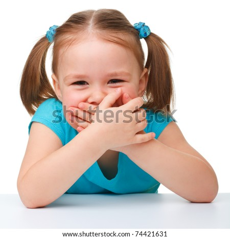 Portrait of a cute little girl covering her mouth with hands, isolated over white