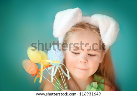 Portrait of a cute little girl dressed in Easter bunny ears holding colorful eggs