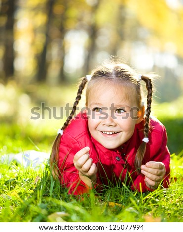 Portrait of a cute little girl in autumn park