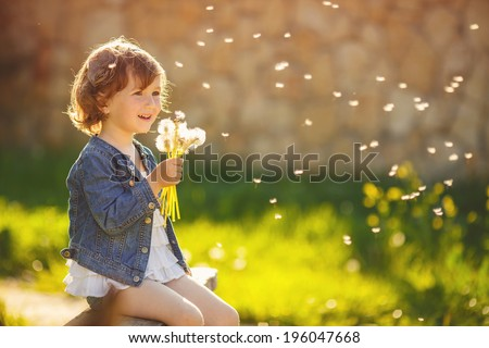 Portrait of a cute little girl in sunny summer day at green nature background