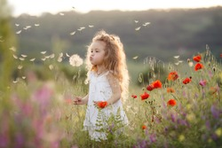 Portrait of a cute little girl in sunny summer day at green nature background. Summer joy - lovely girl blowing dandelion.