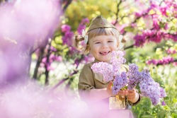 Portrait of a cute little girl in uniform with flowers on a green background. Victory Day, May 9 holiday.