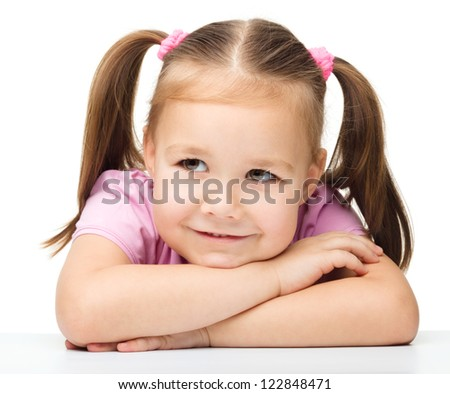 Portrait of a cute little girl sitting at table, isolated over white