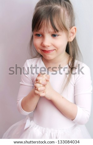 Portrait of a cute little girl smiling, portrait over light grey background