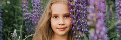 portrait of a cute little happy seven year old kid girl with bloom flowers lupines in a field in nature outdoor. banner