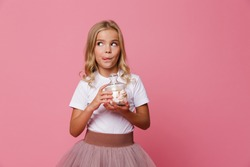 Portrait of a cute little hungry girl holding jar of marshmallow and looking away isolated over pink background
