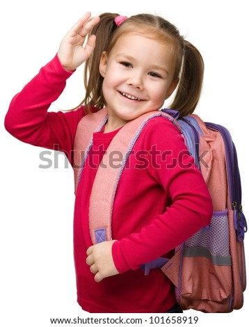 Portrait of a cute little schoolgirl with backpack, going to school and waiving bye-bye, isolated over white