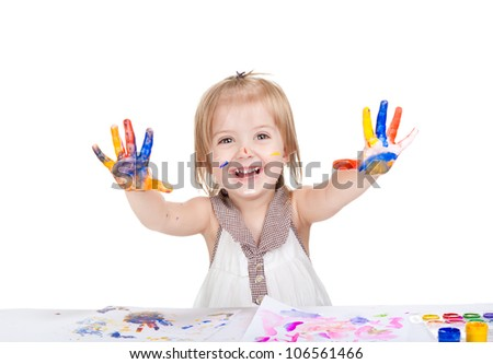 Portrait of a cute little smiling girl with the palms painted by a paint. 2 year happy excited smile child point palm at camera, Isolated on white background