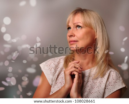Portrait of a cute mature woman dreaming. Close-up face of a middle aged woman  on the background bokeh.