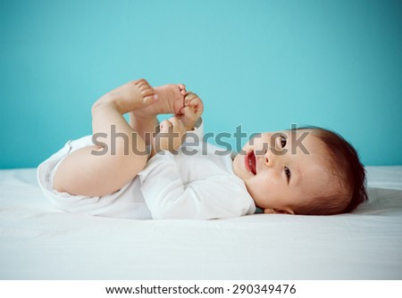 Portrait of a cute 7 months baby lying down on a bed, new family and love concept.