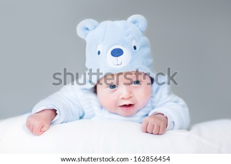 Portrait of a cute newborn baby boy in a teddy bear hat