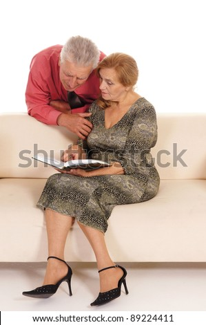 portrait of a cute old woman and man reading at couch - stock photo