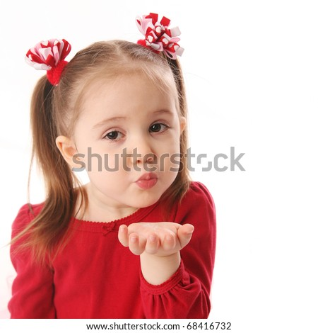 Stock Photo Portrait of a cute preschool girl blowing a kiss, wearing red and pigtails dressed for Valentines day