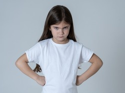 Portrait of a cute pretty child girl looking angry and disappointed with her arms crossed. Isolated on neutral background. In children feelings and behaviour and human emotions and expressions.