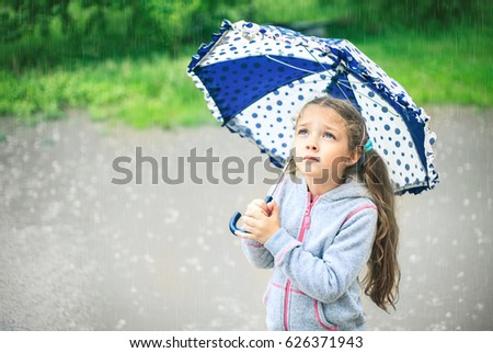 Portrait of a cute sad girl with an umbrella in the rain. #626371943