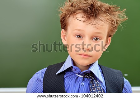 Portrait of a cute schoolboy in a classroom.