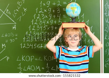 Portrait of a cute schoolboy standing with a book and globe over blackboard.