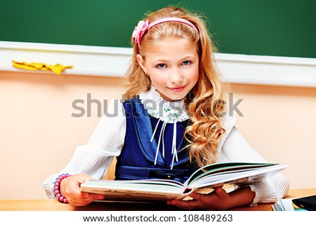 Portrait of a cute schoolgirl in a classroom. - stock photo