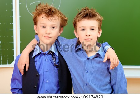 Portrait of a cute shaggy schoolboys in a classroom.