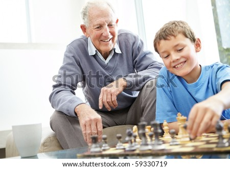Portrait of a cute small boy playing chess with his grandfather