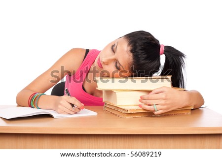 Portrait of a cute teenage girl sleeping on a stack of books at her desk
