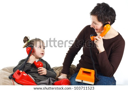 Portrait of a cute 3-year-old girl and her young mother playing, phoning with retro telephones, one red, one orange, looking at each other - isolated on white