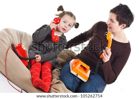 Portrait of a cute 3-year-old girl and her young mother playing, phoning with retro telephones, one red, one orange - isolated on white