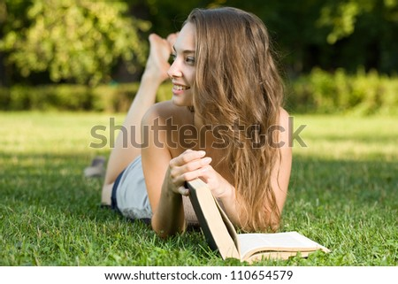 Portrait of a cute young brunette student in the park having fun reading a book.