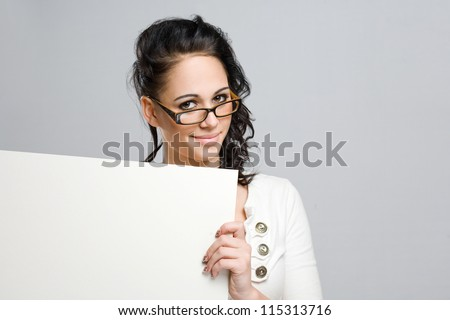 Portrait of a cute young brunette woman with white blank sign.
