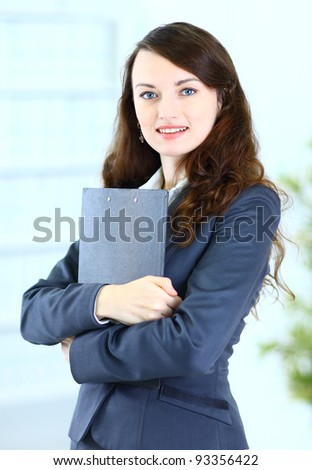 Portrait of a cute young business woman with the work plan smiling, in an office environment.