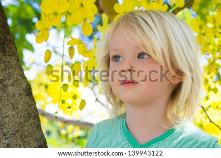 Portrait of a cute young child sitting up in a tree with beautiful yellow flowers