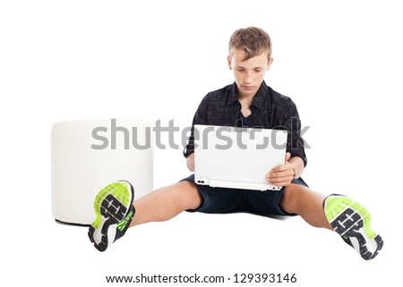 Portrait of a cute young European guy. A guy wearing a black shirt and shorts sitting on the floor in front of the laptop. Studio shot, isolated on white background.
