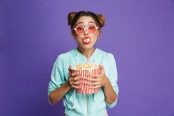 Portrait of a cute young girl with bright makeup isolated over violet background, eating popcorn