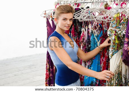 Portrait of a cute young lady shopping for clothes in the mall