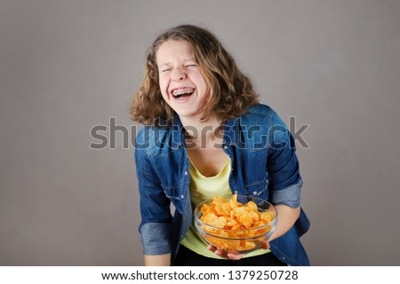 Portrait of a cute young laughing girl  with braces on the teeth holding a glass bowl full of chips.