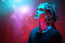 Portrait of a cyborg looking up over red background. Biological human robot with wires implanted in the head. Technologies of the future. Copy space.