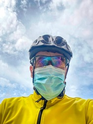 portrait of a cyclist wearing a helmet, glasses and a yellow jacket, riding a bike with a mask on, vertical portrait against a cloudy sky