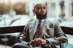 Portrait of a dapper mature hairless black man entrepreneur with a nice beard, in a custom elegant grey costume, sitting in an outdoor cafe on a rainy day and pensively looking into the distance