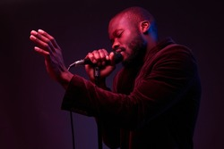 portrait of a dark-skinned handsome guy in dark jacket and t-shirt holds a microphone in his hands and emotionally sings in a dark studio with red and blue light