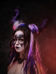 Portrait of a demonic girl wearing scary fantasy make up and violet horns posing in a dark studio on a grey background looking scary