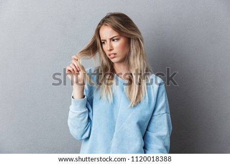 Portrait of a depressed young blonde girl examining her hair isolated over gray background