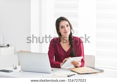 Portrait of a designer working home on new ideas A dark hair braided woman is sitting at a white table in casual clothes, she is looking at camera, holding her tablet and with her laptop next to her
