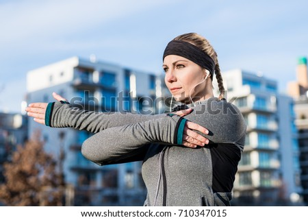 Portrait of a determined young woman stretching her left arm during warm-up routine before outdoor workout in a sunny day #710347015