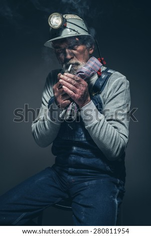 Portrait of a Dirty Adult Gold Miner Sitting on a Stool with his Helmet, Lighting his Cigarette While Looking at the Camera.