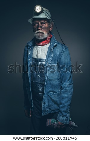 Portrait of a Dirty Senior Male Gold Miner, Wearing Denim Jacket and Helmet with Light, Holding his Gloves and Looking at the Camera Against Gray Gradient Background.