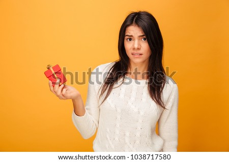 Portrait of a disappointed young woman holding small gift box isolated over yellow background Stockfoto ©