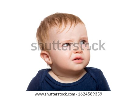 Portrait of a disgruntled child looking incredulously to the side with frowning eyebrows, close-up of a toddler isolated on a white background. Сток-фото ©